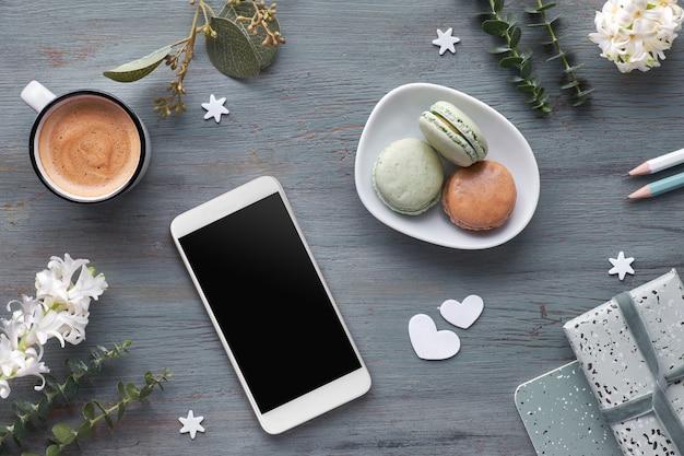 Весенняя плоская планировка с жемчужными цветами гиацинта, эвкалиптом, мобильным телефоном и подарком