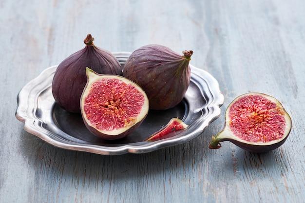Свежие фрукты - инжир в металлической пластине на деревенском дереве