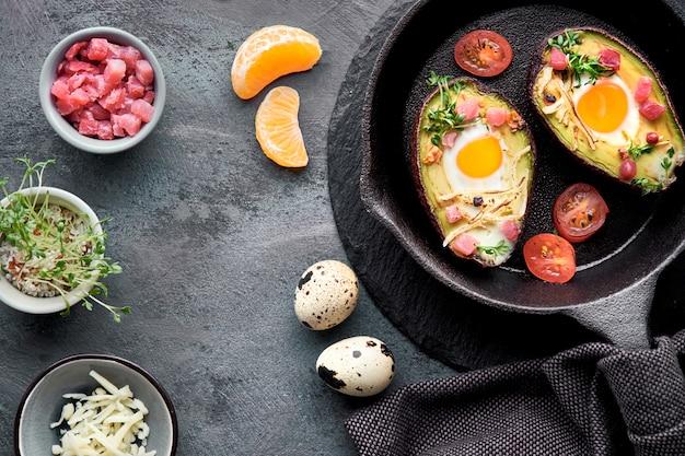 Кето диетическое блюдо: авокадо лодки с ветчиной кубиками, перепелиными яйцами, сыром