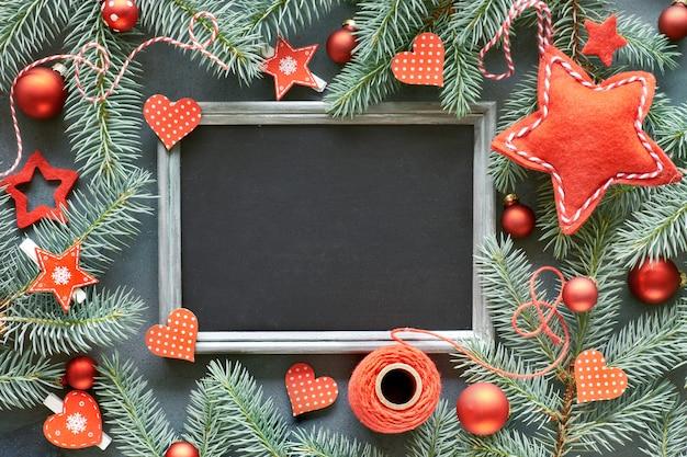 Рождественский фон с еловыми ветками, красными безделушками, звездами и сердцами вокруг пустой доски