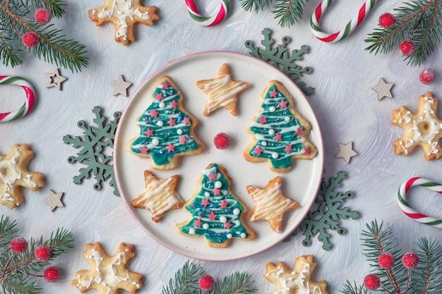 モミの小枝、キャンディー、雪片、ベリー、フラットレイアウトのクリスマスクッキー