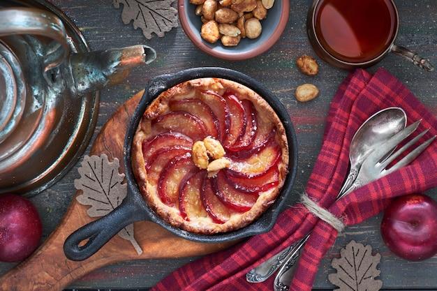 Домашний сливовый пирог, запеченный в чугунной сковородке, подается с арахисом по дереву