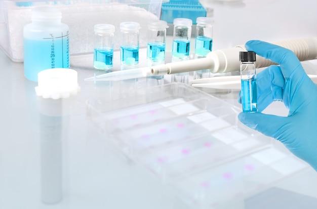 液体サンプル、ガラス管および皿に入った青い液体サンプル
