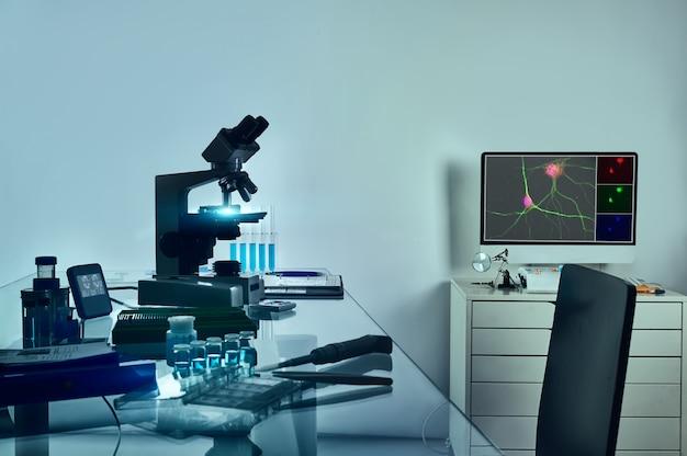 顕微鏡、神経細胞のデジタル蛍光画像とコンピューターテーブル、ガラステーブル上の組織学的固定ツール。