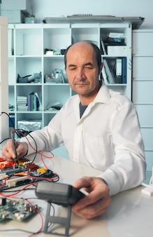 シニア男性技術者が電子機器をテスト