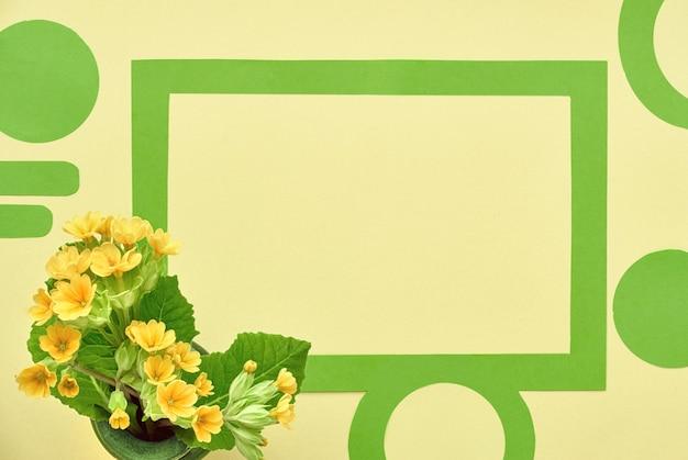 Рамка из зеленой бумаги, украшенная пряниками, желтыми цветами и листьями первоцвета, копия пространства