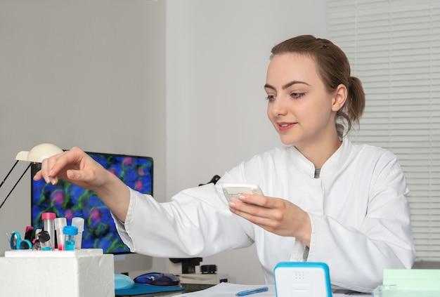 若い女性科学者または技術者が研究施設で働いています