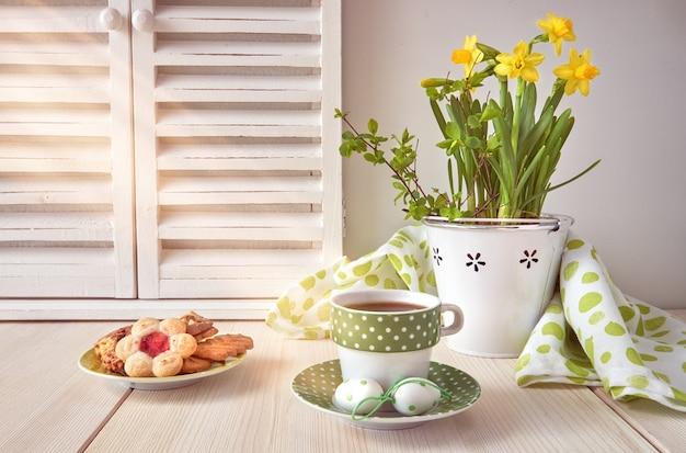 黄色い水仙、コーヒー、明るい色の木製のクッキーと春のグリーティングカードのデザイン