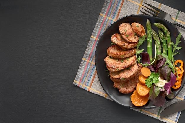 黒い板の牛肉、サツマイモ、ミックスサラダのフライスライス、暗いスレート、コピースペースの食事の設定