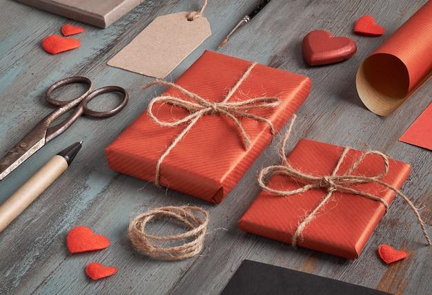 Упакованный подарок, упаковочная бумага, этикетки и украшения на деревенский деревянный стол