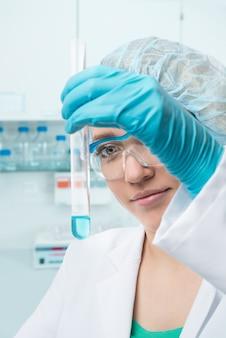 若い女性技術者または科学者の試験管に液体サンプル