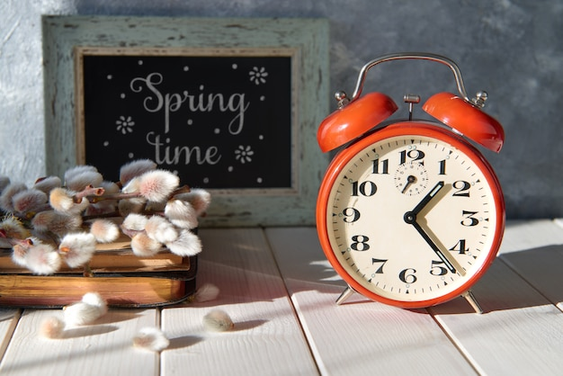 赤い目覚まし時計、古い本と言葉に猫柳の花