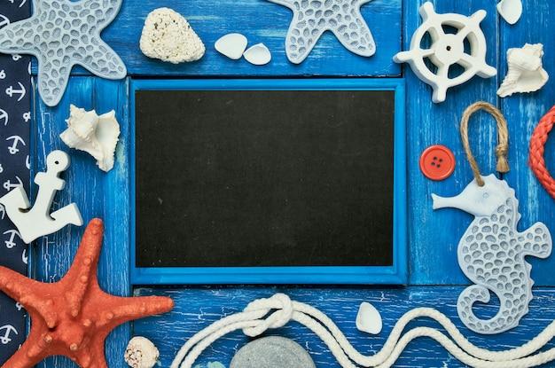 海の貝殻、石、ロープ、青い木製の背景、コピースペースに星の魚と空白の黒板