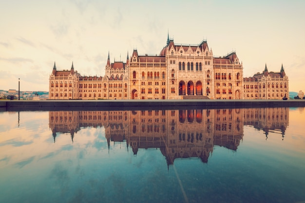 反射と日の出のブダペストの国会議事堂