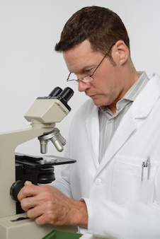 成熟した科学者は顕微鏡で働いています