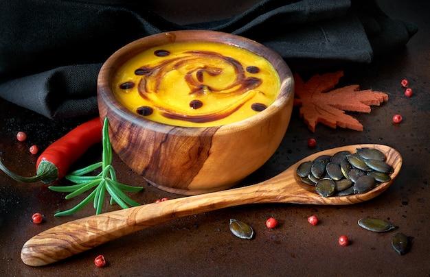 暗い木製ボウルでスパイシーなカボチャのスープ、木製ボウルで提供しています