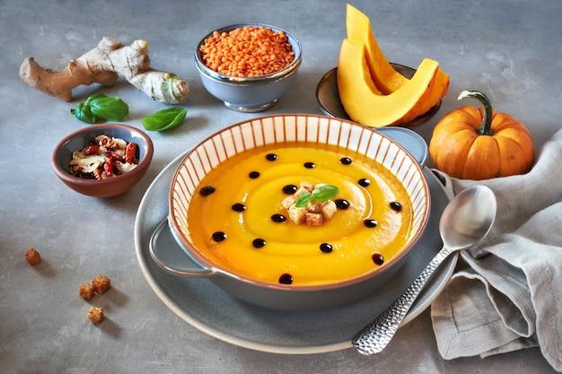 ストライプのセラミックプレートにクルトンとバルサミコ酢を添えたおいしいパンプキンクリームスープ