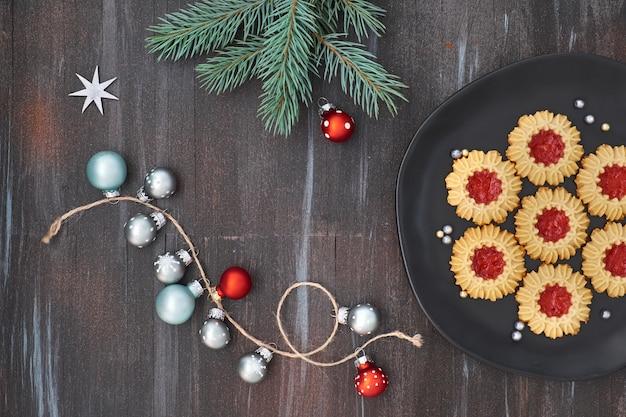 灰色と赤のクリスマスデコレーションと暗い灰色の木のジャムクッキーでフラットレイアウト