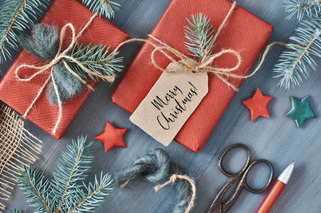 モミの枝とクリスマスの素朴な木製のプレゼントは赤い紙に包まれた贈り物