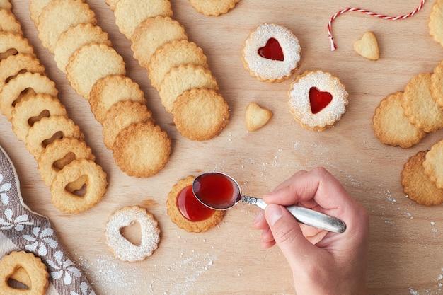 木の板にイチゴのジャムで満たされた伝統的なクリスマスリンツァークッキーの平面図。