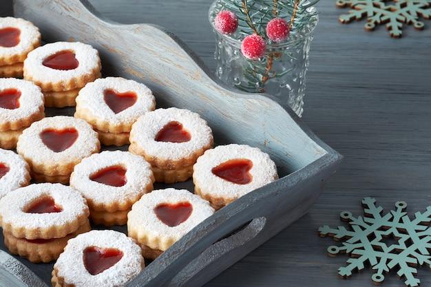 装飾された木製のテーブルの上のコンクリートプレートにいちごジャムで満たされた伝統的なクリスマスリンツァークッキーのクローズアップ