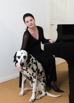 Молодой музыкант со своей собакой у фортепиано