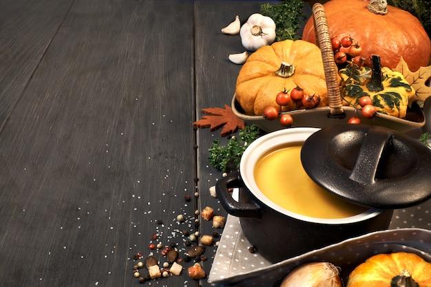 暗闇の中で暗いセラミック鍋にカボチャのクリームスープ