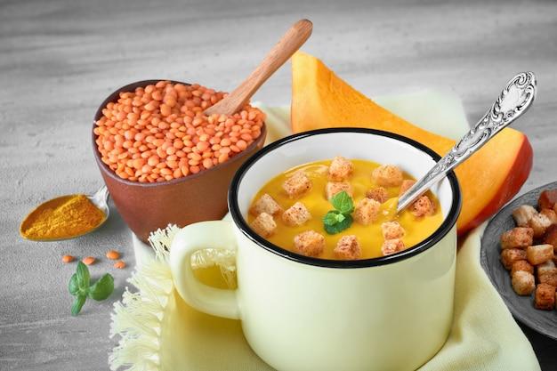 おいしいナプキンに明るい黄色のマグカップでクルトンを添えたおいしいパンプキンクリームスープ