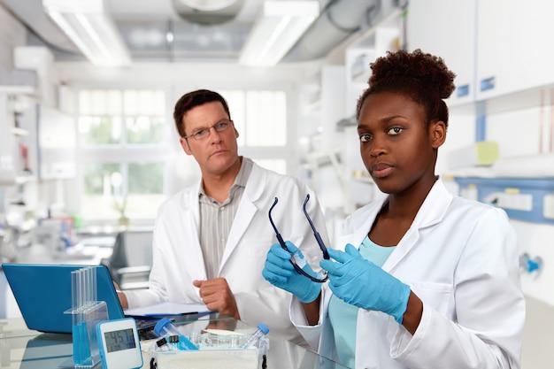 科学者、白人の男性とアフリカの女性、研究室で働く