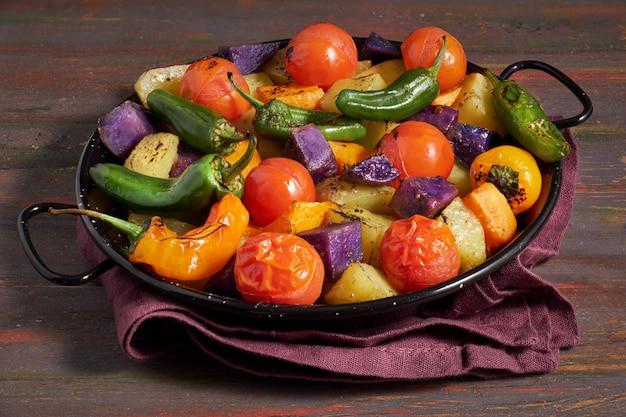 素朴なオーブン焼き野菜のグラタン皿。リネンタオルで暗い木製の季節のベジタリアンビーガン食事