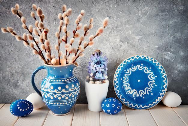 Букет из вербы в синем керамическом кувшине с подходящей тарелкой, пасхальными яйцами и весенним украшением
