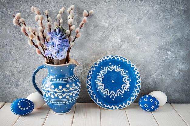 マッチングプレート、イースターエッグ、グレーの春の装飾が付いた青いセラミックピッチャーのネコヤナギの束