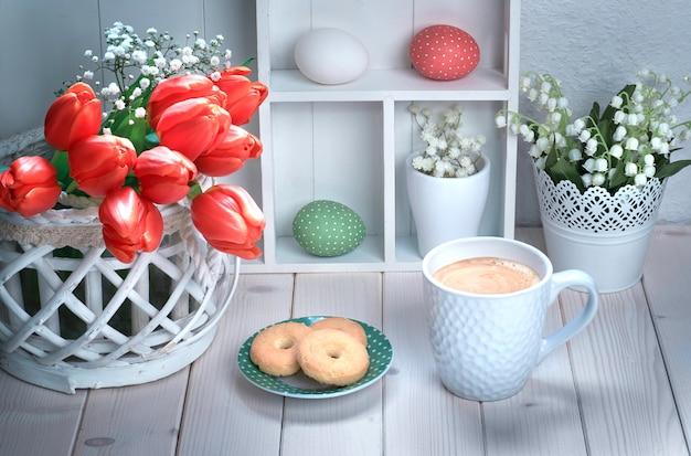 一杯のコーヒーと赤いチューリップと白い木製のテーブルの上のクッキー