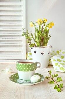 黄色い水仙と明るい木のコーヒーカップと春のグリーティングカードのデザイン