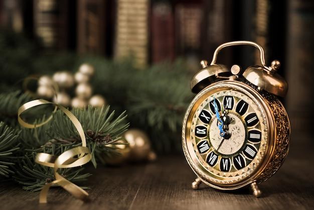 Старинные часы на праздничном фоне, показывающие пять до полуночи