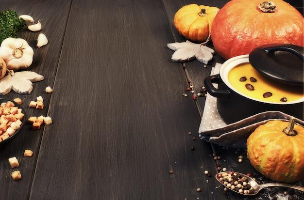 暗い背景に暗いセラミック鍋にカボチャのクリームスープ