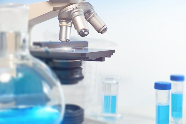 光学顕微鏡とぼやけた実験室へのクローズアップと科学的背景