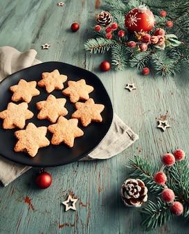 Деревенский рождественский фон в зеленый и красный с печеньем и украшениями