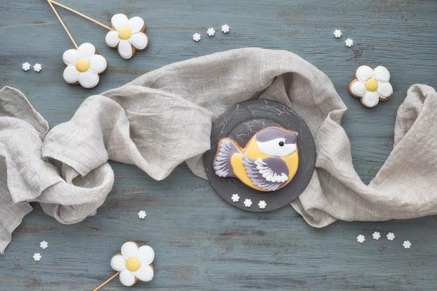 Пряники в форме синицы и цветы на серой деревянной доске