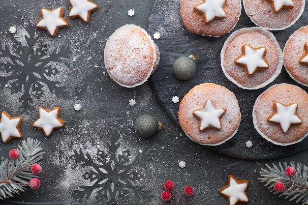 Вид сверху на стол с посыпанными сахаром маффинами и печеньем рождественской звезды