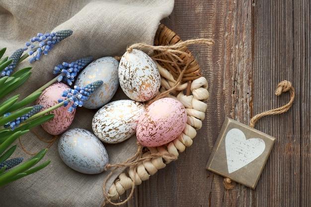 Деревенская пасха с яйцами синих цветов гиацинта и деревянного сердца, вид сверху