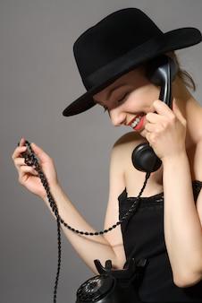 Портрет молодой привлекательной молодой женщины, выступая на старинный черный телефон