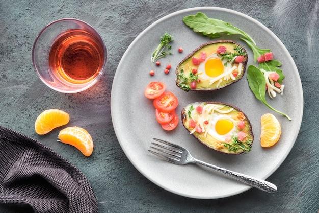 Кето диетическое блюдо: авокадо лодки с ветчиной кубиками перепелиные яйца, сыр