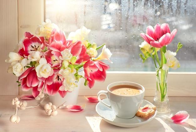 コーヒーカップピンクチューリップと白いフリージア-窓板、春