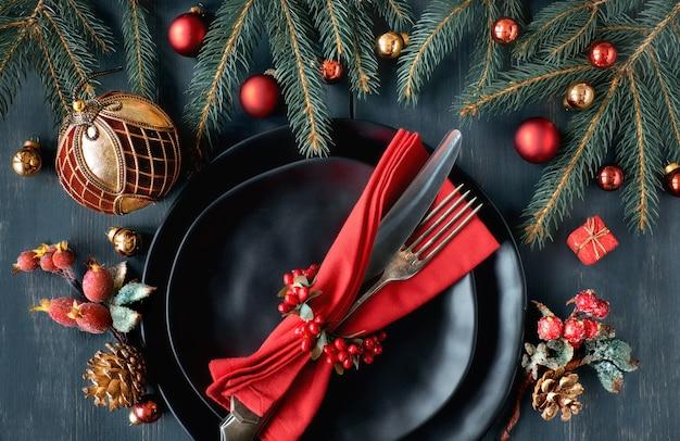 Черные тарелки и винтажные столовые приборы с елочными украшениями зеленого и красного цвета
