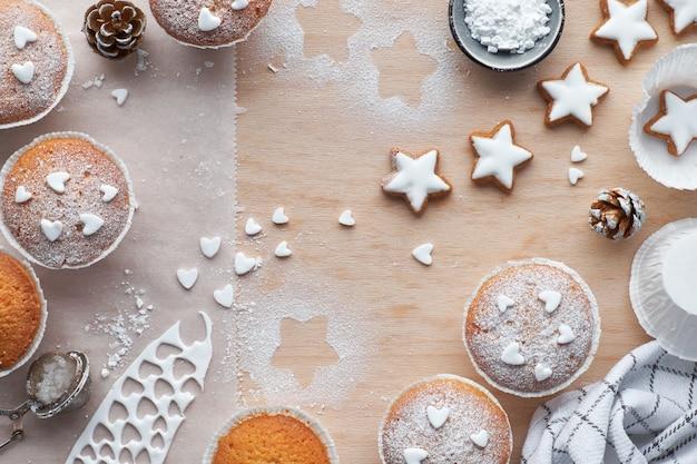 Вид сверху на стол с посыпанными сахаром маффинами, помадной глазурью и печеньем из рождественских звезд