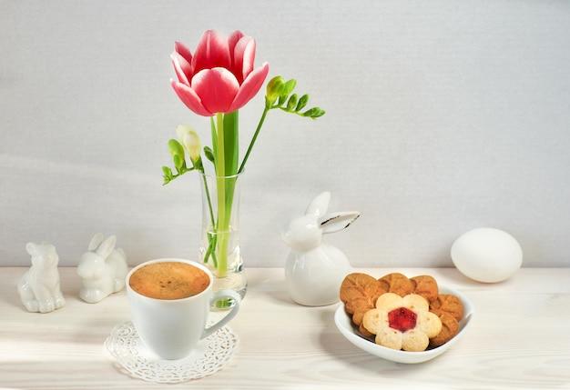ガラスの花瓶、イースターバニー、エスプレッソ、葉と花の形をしたクッキーの春の花