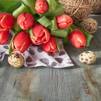 Весенний фон празднования: букет красных тюльпанов, весенние украшения и крашеные яйца на серой деревенской доске.