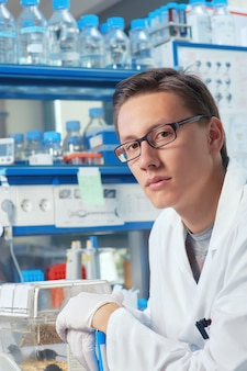 男性科学者または大学院生が研究室で働いています