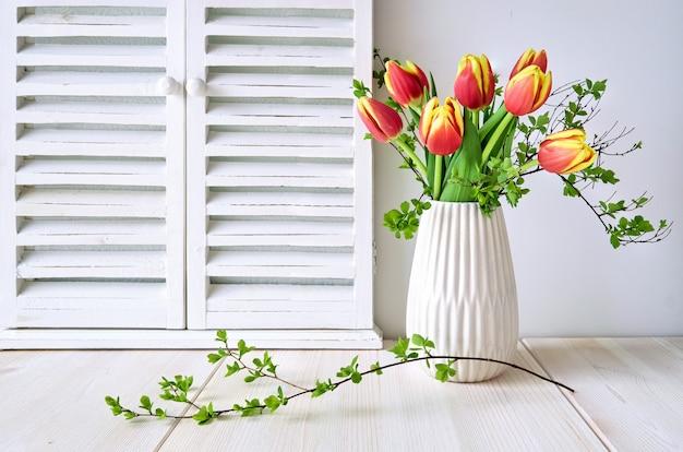 Весенний дизайн поздравительной открытки с букетом красных тюльпанов и весенними листьями на светлом дереве